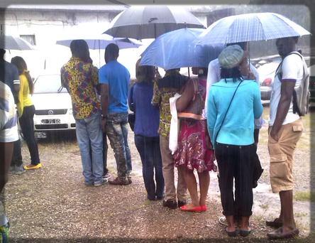 des gens en rang sous la pluie