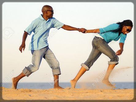 un homme qui joue avec sa copine à la plage