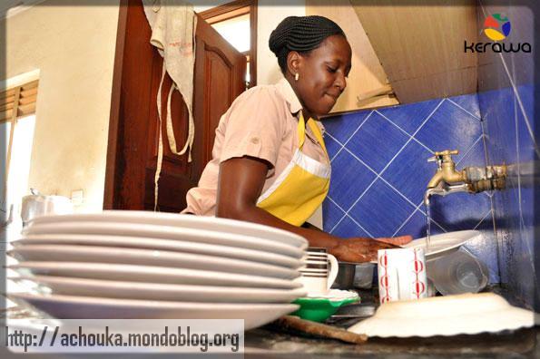 une femme de ménage noire qui fait la vaisselle