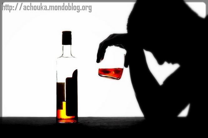 un homme devant une bouteille d'alcool