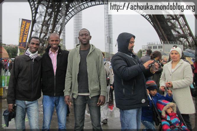 trois mbeinguètaires devant la tour Eiffel