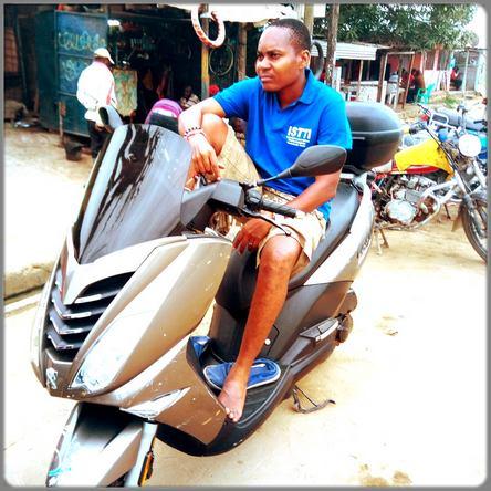 Ecclésiaste Deudjui sur sa moto scooter
