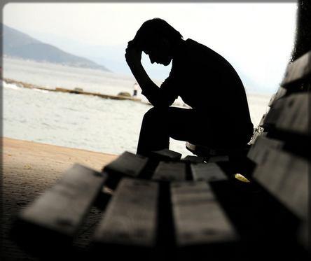 un homme triste sur un banc public