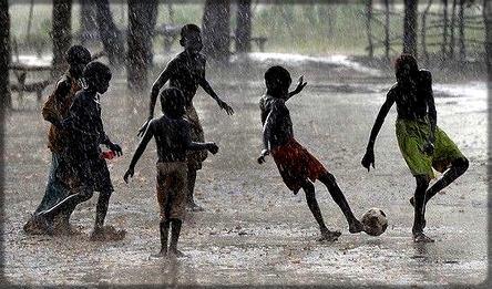 des enfants qui jouent au football sous un temps de pluie