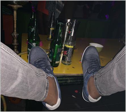 deux pieds sur une table remplie de bières