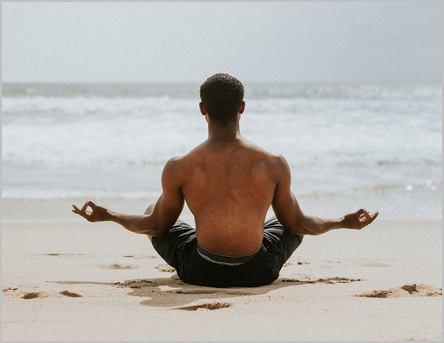 homme noir qui médite sur la plage